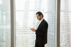 Serious businessman in modern office near window looking at cell. Young handsome businessman in expensive dress suit in modern office next to the window is Royalty Free Stock Image
