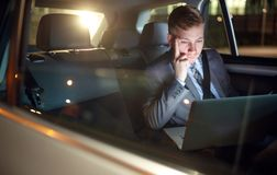 Serious businessman in moving car working on his laptop. Serious businessman in moving car working overtime on his laptop Stock Photography