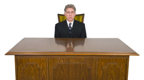 Serious Businessman, Office Desk, Chair, Isolated. Serious businessman sits at an empty business office desk and chair. Desk is made of wood. Isolated on white Stock Images