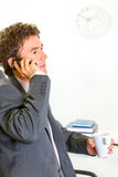 Serious businessman in office talking mobile Stock Photography