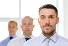 Serious businessman in office with team on back Royalty Free Stock Photo