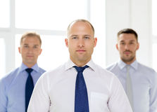 Serious businessman in office with team on back Stock Images