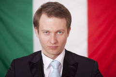Serious businessman over italian flag Royalty Free Stock Photos