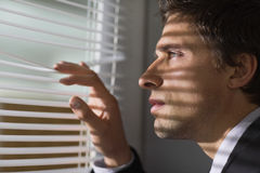 Serious businessman peeking through blinds in office Stock Images