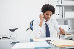 Serious businessman on the phone at desk Royalty Free Stock Photography