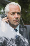 Serious businessman on the phone driving Stock Photo