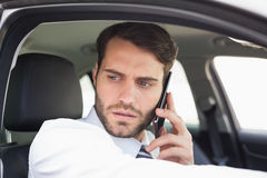 Serious businessman on the phone. In his car Royalty Free Stock Photos