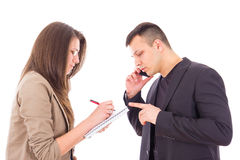Serious businessman on the phone and his secretary. Writing down notes Royalty Free Stock Photos