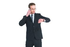 Serious businessman phoning while checking time Stock Images