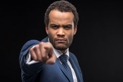 Serious businessman pointing at camera isolated on black Stock Images