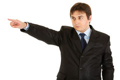 Serious businessman pointing finger in corner Royalty Free Stock Images