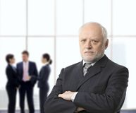 Serious businessman portrait. Portrait of serious senior businessman standing with arms folded in office lobby, colleagues in background Stock Photography
