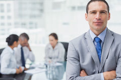 Serious businessman posing with coworkers on background Royalty Free Stock Images