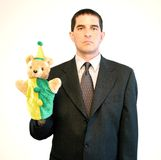Serious Businessman with Puppet. Serious-looking businessman holding a puppet royalty free stock images