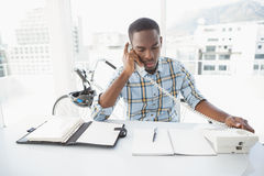 Serious businessman reading desk diary and phoning Stock Photography
