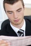 Serious businessman reading the newspaper Royalty Free Stock Image