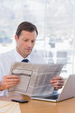 Serious businessman reading a newspaper Royalty Free Stock Images