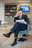 A serious businessman reading a newspaper Stock Photos
