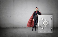 A serious businessman in a red cape and an eye mask leaning on a big metal strongbox. Royalty Free Stock Photos