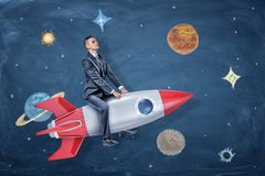 A serious businessman rides a silver and red rocket among the drawings of planets and stars. stock photos