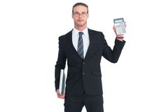 Serious businessman showing calculator holding laptop. On white background royalty free stock photography
