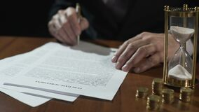 Serious businessman signing purchase agreement as time flows with sand in clock. Stock footage stock footage