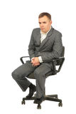 Serious businessman sits on chair stock images