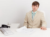 Serious businessman sits on workplace at office Royalty Free Stock Photos