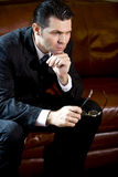 Serious businessman sitting on couch thinking Royalty Free Stock Photography