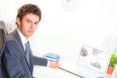 Serious businessman sitting at desk with laptop Royalty Free Stock Photo