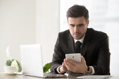 Male business leader browsing online resources using gadgets. Serious businessman sitting at desk with laptop and using digital tablet. Executive manager reading Royalty Free Stock Photography