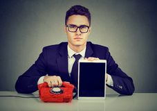 Serious business man sitting at desk with old fashioned telephone and modern tablet. Serious businessman sitting at desk with old fashioned telephone and modern Stock Photos