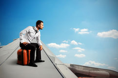 Serious businessman sitting on his bag Royalty Free Stock Image