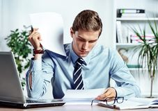 Serious businessman sitting at his desk reading a documents. Photo of successful man working in the office. Business concept Royalty Free Stock Photography