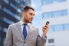 Serious businessman with smartphone outdoors Royalty Free Stock Photo