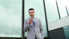 Serious businessman with smartphone outdoors Stock Images