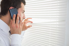 Serious businessman spying through roller blind while phoning Royalty Free Stock Photo