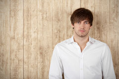 Serious Businessman Standing Against Wooden Wall Stock Photography
