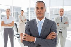 Serious businessman standing with arms crossed Stock Photos