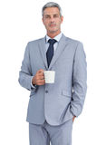 Serious businessman standing with coffee Royalty Free Stock Photos