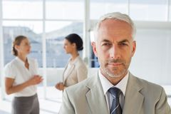 Serious businessman standing while colleague are discussing toge Stock Image