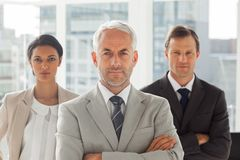 Serious businessman standing with colleagues behind Stock Photos