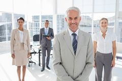 Serious businessman standing with colleagues Royalty Free Stock Photography