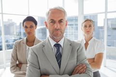 Serious businessman standing in front of colleagues Stock Images