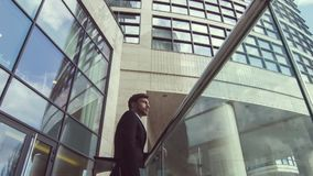 Serious businessman standing near office building. Urban style. Professioanl serious businessman standing near office building and thinking about work while stock footage