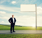 Serious businessman standing on the road Stock Photography