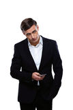 Serious businessman standing with smartphone Stock Photo