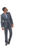 Serious businessman stepping ahead and looking up. On white background Stock Photos