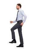 Serious businessman stepping on imaginary step Stock Photos