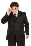 Serious businessman straightening eyeglasses Stock Photos
